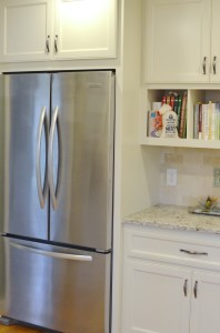 A stainless steel refrigerator is nestled between custom cabinets in this white kitchen