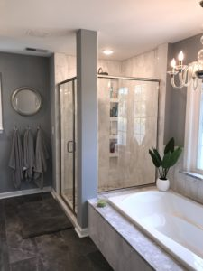 Carrara marble shower with semi-frameless glass shower door.