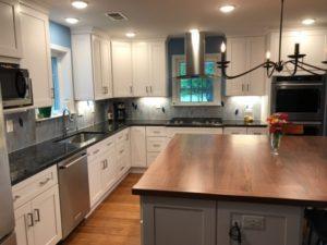 White Shaker cabinets, black walnut island top, granite countertop with tile backsplash, recessed and under-cabinet lighting.