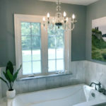 Soaking tub equipped with integral lumbar support and armrests for comfort, marble surround and picturesque view of horse farm; classic chandelier.
